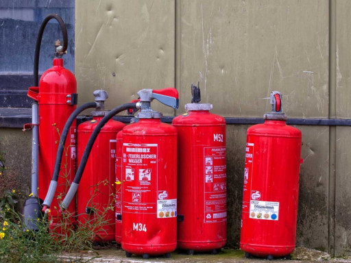 Five red fire extinguishers standing up against the wall.
