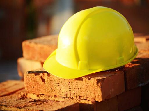 Yellow hard hat on bricks.