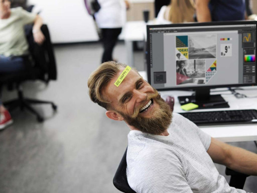 Man sat in a chair smiling with a post it note on his head.