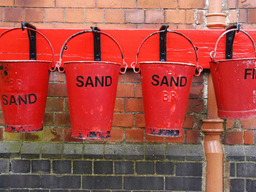 Several sand buckets hanging on wall.